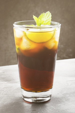 Cocktail Cuba Libre in a glass on a dark background. Toning Stock Photo