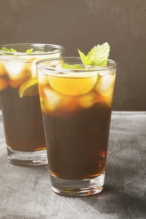 Two glasses of cocktail Cuba Libre on a dark background. Toning