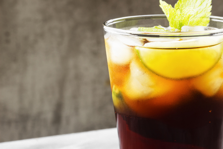 Cocktail Cuba Libre in a glass on a dark background. Copy space. Food background Stock Photo