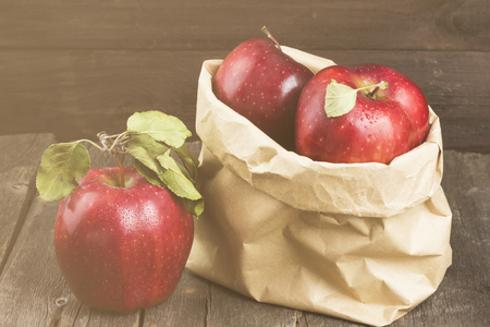 Apples in paper package on a dark wooden background. Toning