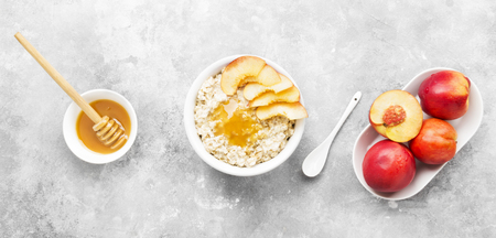 Oatmeal with nectarine and honey on a gray background. Top view. Food background Stock Photo