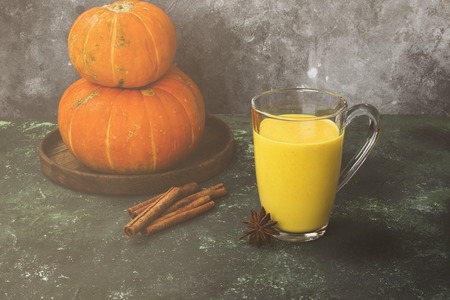 Pumpkin latte with spices (cinnamon, anise) on a green background. Toned Stock Photo
