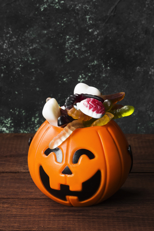 Terrible sweets for Halloween in decorative pumpkin on a dark background