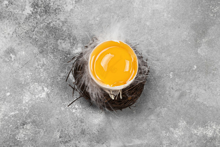 Egg yolk in nest on a gray background. Top view. Food background Standard-Bild
