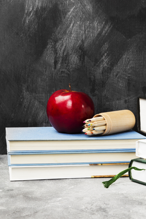 School attributes - books, colored pencils, notebook, apple on dark background Archivio Fotografico - 96999164