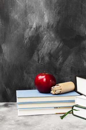 School attributes - books, colored pencils, notebook, apple on dark background