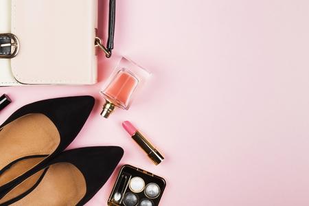 Accessoires pour femmes - chaussures, sac, cosmétiques, parfum sur fond rose. Contexte féminin et mode. Vue de dessus, espace copie