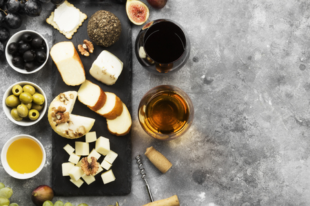 Snacks with wine - various types of cheeses, figs, nuts, honey, grapes on a gray background. Top view, copy space. Food background