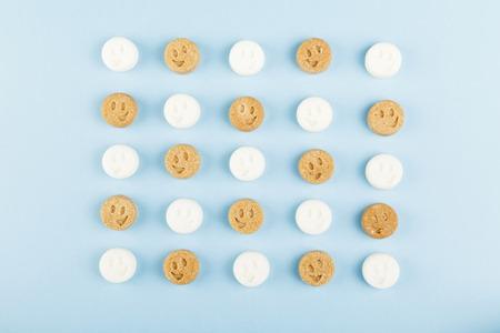 Witte en bruine suiker glimlacht op blauw