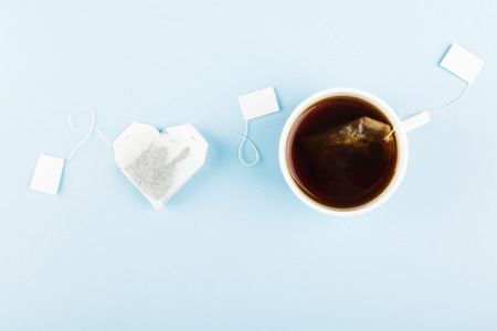 Cup of tea and tea bags in form of heart on blue Фото со стока