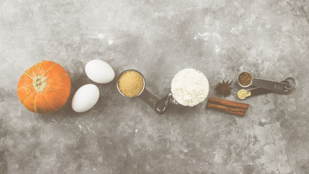 Ingredients for pumpkin pie - flour, pumpkins, eggs, cane sugar, various spices (nutmeg, ginger, cinnamon, anise) on a gray