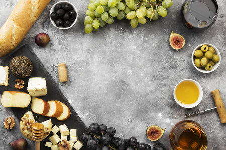 Snacks with wine - various types of cheeses, figs, nuts, honey, grapes, bread on a gray background. Top view, copy space. Food background