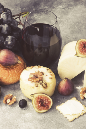Snacks with wine - various types of cheeses, figs, nuts, honey, grapes on a gray background. Toned