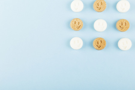 White and brown sugar smiles on blue background. Top view, copy space. Food background