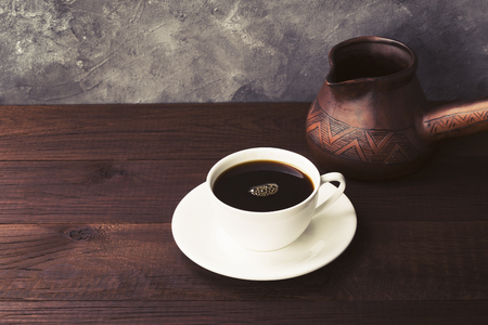 Coffee in white cup and clay cezve on wooden background. Toned