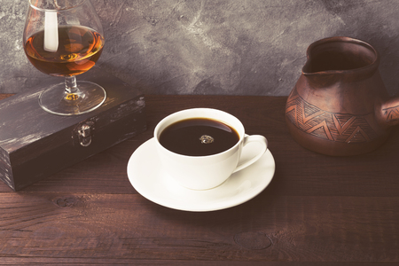 Coffee in white cup with cognac and clay cezve on wooden background. Toned