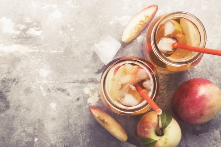 Peach nectarine cold ice tea lemonad different ingredients two glasses jar on gray background.