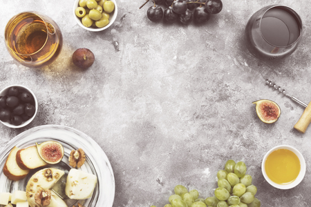 Snacks with wine - various types of cheeses, figs, nuts, honey, grapes on a gray background. Top view, copy space. Food background. Toned 스톡 콘텐츠
