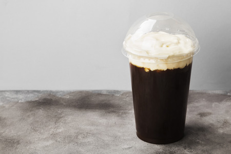 Coffee in plastic takeaway cup with cream on gray background. Copy space. Food background
