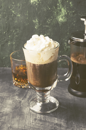 Irish coffee with whisky on dark background. Toned