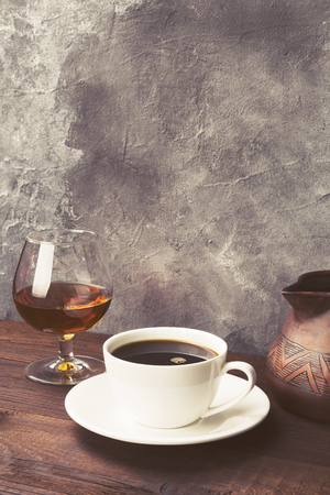 Coffee in white cup with cognac and clay cezve on wooden background. Copy space. Food background. Toned