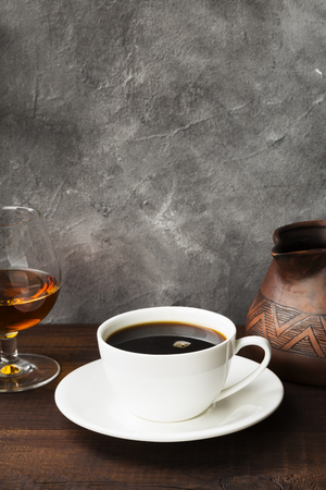 Coffee in white cup with cognac and clay cezve on wooden background. Copy space. Food background