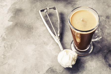 Ice coffee with ice cream on gray background. Copy space. Food background. Toned 写真素材