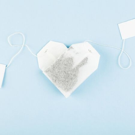 Tea bags in form of heart on blue background. Top view. Food background