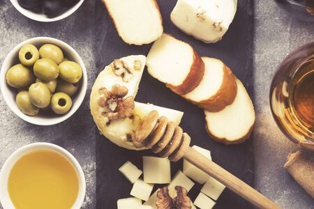 Snacks with wine - various types of cheeses, figs, nuts, honey, grapes on a gray