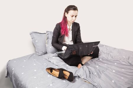 Concept - work from home, self-isolation, quarantine. Young girl in black suit sits in bed, holding laptop on her knees