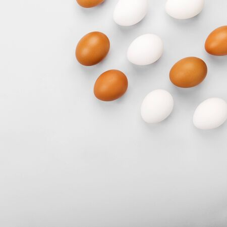 Group of raw eggs white and brown. Concept of diversity, isolation, racism, inequality. On gray background. Top view, copy space