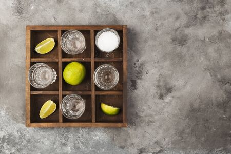 Tequila shots, limes and salt on wooden board on grey background. Top view, copy space