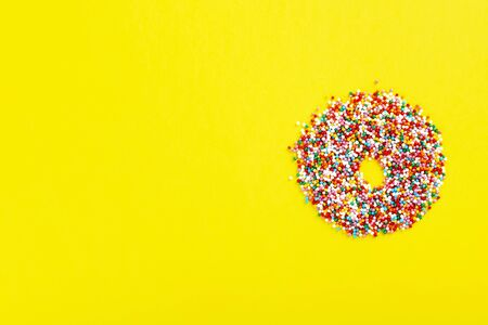 Multicolored sugar pastry topping in form of donut on yellow background. Funny food. Top view. Copy space