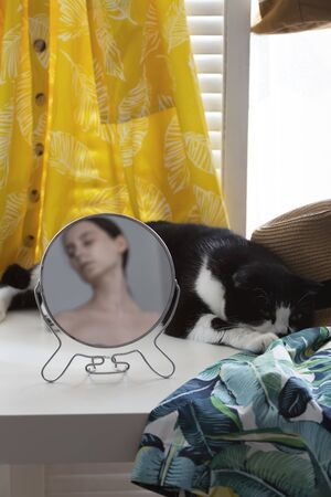 On table near window sleeps cat around clothes in circular mirror reflects woman out of focus