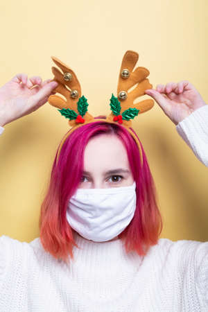 Girl in white sweater and deer horns on head, wearing protective mask on face, yellow background