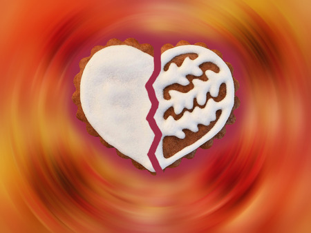 Broken heart - gingerbread cookie on multicolor blurred background Imagens