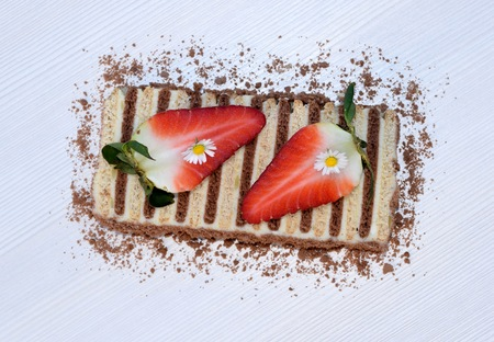 Slice of unbaked layered dessert made of flat biscuits and curd, decorated with daisies and strawberries