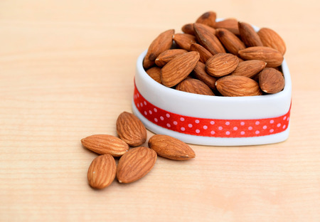 Almonds in ceramic bowl of heart shape