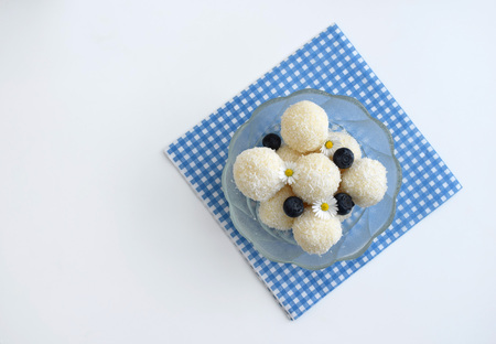 Homemade unbaked coconut balls decorated with blueberries and daisy flowers
