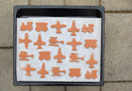 Cut gingerbreads in a shape of airplane, helicopter and train on a baking tray ready for baking