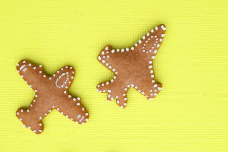 Ginger breads in a shape of airplane on bright yellow Фото со стока