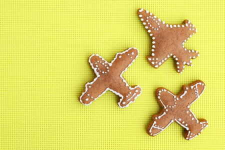 Gingerbreads in a shape of airplane on bright yellow background
