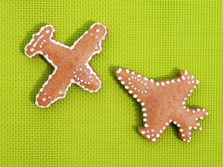 Gingerbreads in a shape of airplane on bright green background