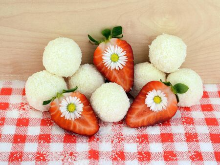 Romantic composition - homemade coconut balls, strawberries and daisy flowers. Everything you can eat