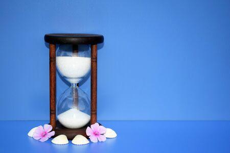 Concepto romántico con reloj de arena, flores y conchas marinas, espacio para copiar texto