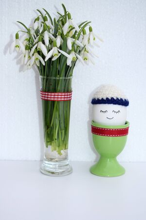 Easter concept with romantic bouquet of snowdrops (Galanthus nivalis) and cute egg