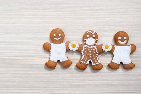 One man with a face mask and two others without it - be considerate and protect people around you - wear a mask. Creative gingerbread concept in coronavirus (COVID-19) time