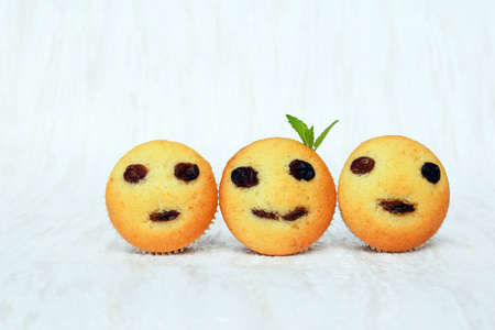 Freshly baked homemade muffins with funny faces. Vanilla muffins with raisins, decorated with melissa leaves