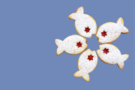 Five linzer cookies in a shape of fish isolated on blue background, top view, copy space for text