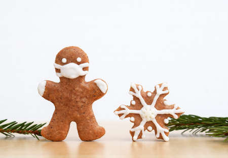Gingerbread man with protective face mask, snowflake and spruce twigs. Copy space